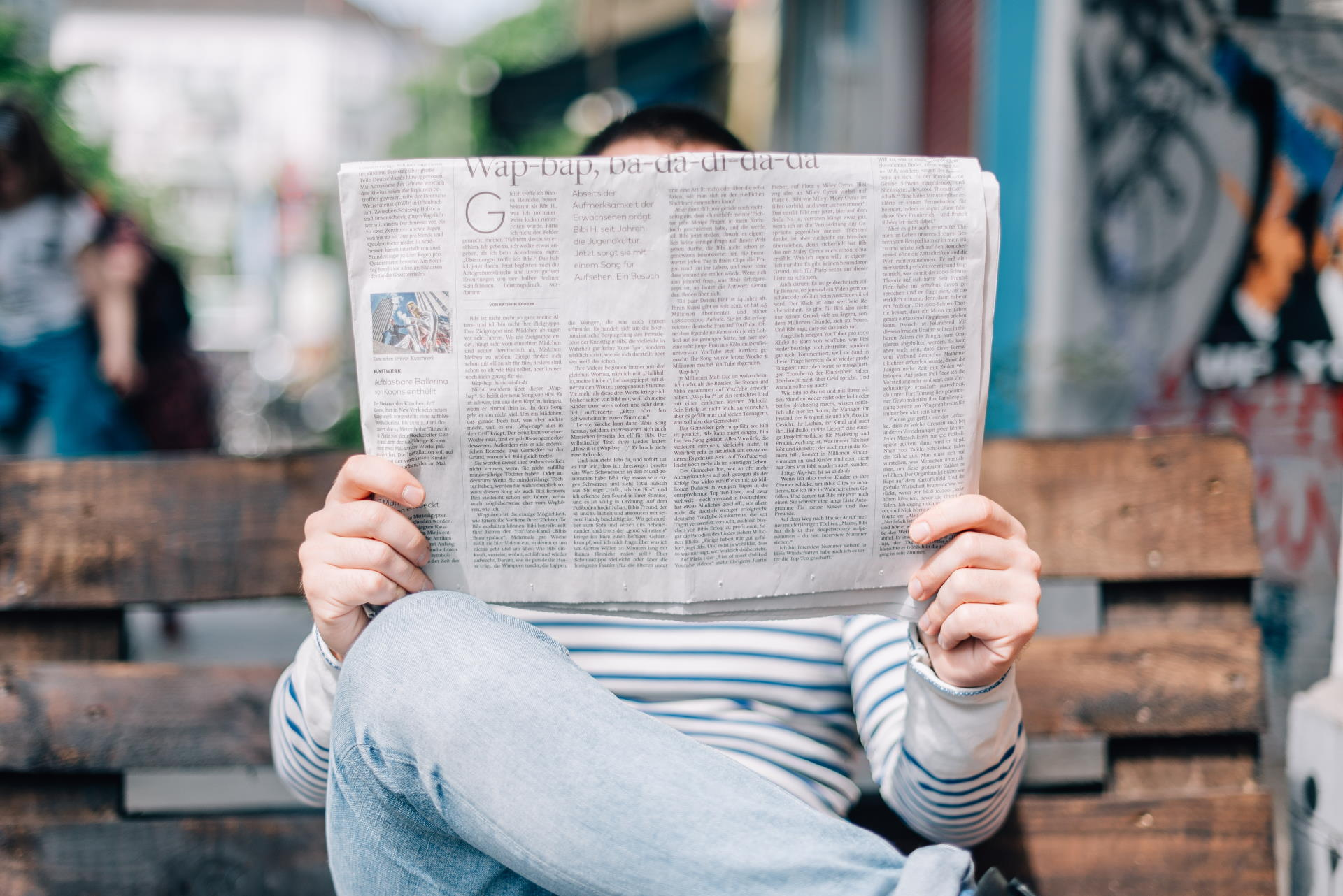 Image of man reading a newspaper to direct to news page